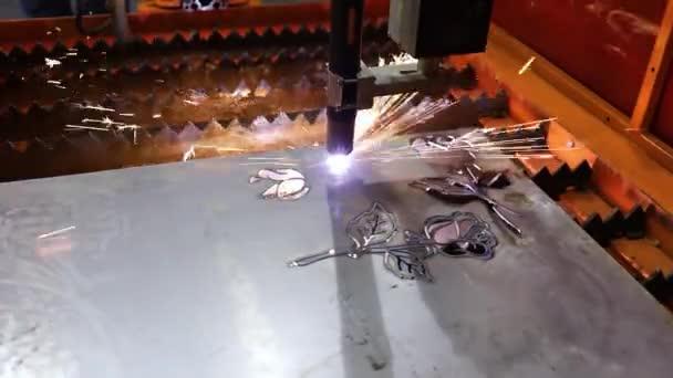Automatizovaný naprogramovaný stroj pro zpracování kovů. Průmyslový laserový stroj vyřezává díly z plechu. Teplo. jiskry během provozu výrobního stroje v závodě.