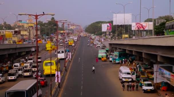 Provoz a chodci křížení silnice a autobusy na stojanu v Indii.