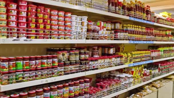 Chennai, Indie-duben 05, 2019: pohled na regály s barevným úložištěm, mnoho koláčků a cukroví, omáček, police na jídlo v supermarketu zásobené sklenkami.