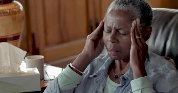 schwarze Baby-Boomer-Seniorin reibt ihre Schläfen, um Kopfschmerzen zu lindern