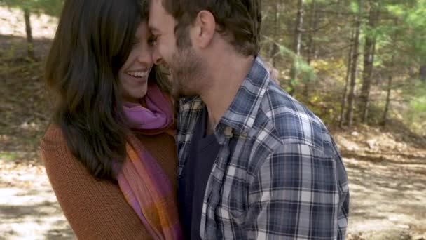 Attractive couple in love kissing, laughing and hugging in a forest