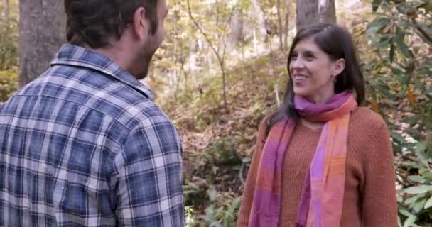 Nő és férfi barátai ölelgetés és üdvözlés egymást a parkban vagy erdőben