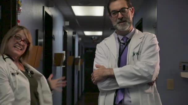 Pošetilý veselý ženský doktor tancující vedle usměvavé mužské doktorky