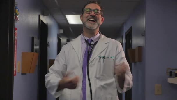 Smiling happy male doctor acting confused with open arms in a hospital or clinic