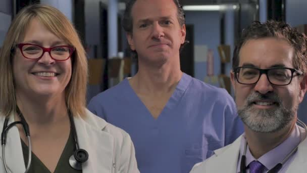 Two male doctors and a female doctor looking at the camera in slow motion