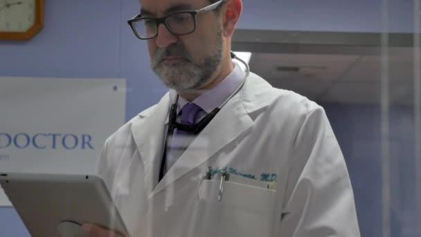 Männliche und weibliche Ärztin Beratung eines digitalen Tablets in einem modernen medizinischen Büro