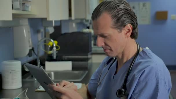 Male nurse or physician reviewing medical records on a digital tablet