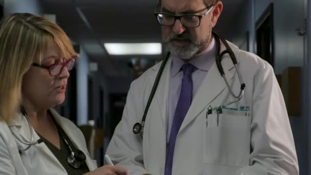 Two doctors consulting with each other while looking at a clipboard