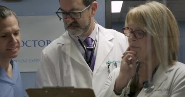 Three doctors collaborating on a case in a modern clinic or hospital