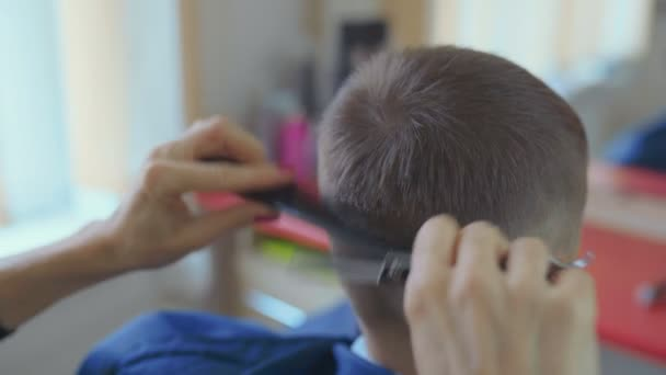 Hairdresser cutting hair with barber scissors in children hairdressing salon.