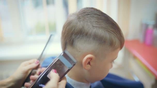 Hairdresser cutting hair with barber scissors in children hairdressing salon.