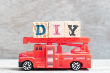 Red fire truck hold letter block in word DIY (abbreviation of do it yourself) on wood background