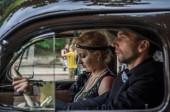 Lviv, Ukraine - Juni 2018: Mann und Frau in einem Retro-Auto im Stil der 30er Jahre
