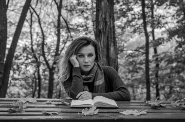 Young beautiful girl sitting in autumn park behind a wooden table reading a book