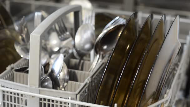 Muž dostává čisté nádobí z myčky nádobí