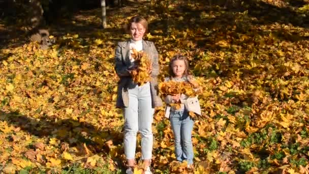 Mom and her daughter little charming girl child throw up fallen yellow maple leaves in autumn park, happy family