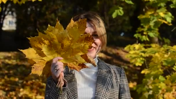 Cute young cheerful and happy girl hides her face behind a yellow maple leaf in autumn park