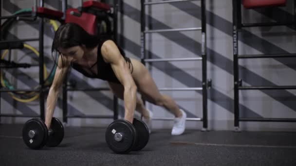 Athletic girl performs strength push-ups from the floor with dumbbells.