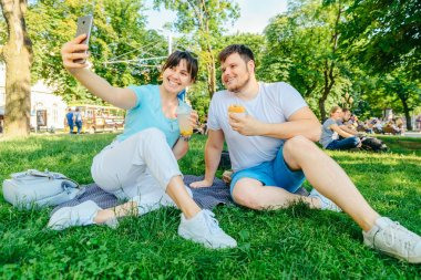 couple sitting on green grass eating burgers drinking smoothie. wide angel