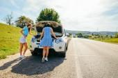dvě ženy u silnice potřebují pomoc s rozbité auto. cestování autem