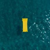 Letní dovolená koncept. žlutý nafukovací matrace v modré moře azurové vody.