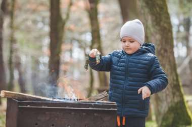 little boy kid put branches in fire into grill