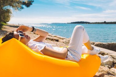woman resting at yellow inflatable air sofa at the sea beach in sunny day