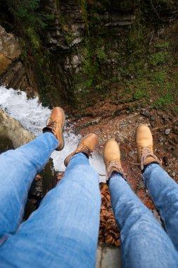 couple sitting on edge looking on waterfall