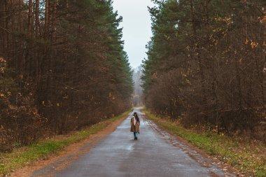 woman walking by empty autumn road