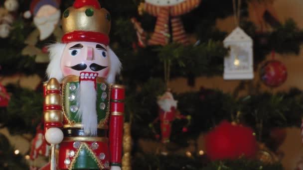 Velká plechová Louskáček vojáku na vánoční stromeček s rozmazané pozadí. Sezónní hračka postava před osvětleným umělý vánoční stromek s světla a barevné dekorace