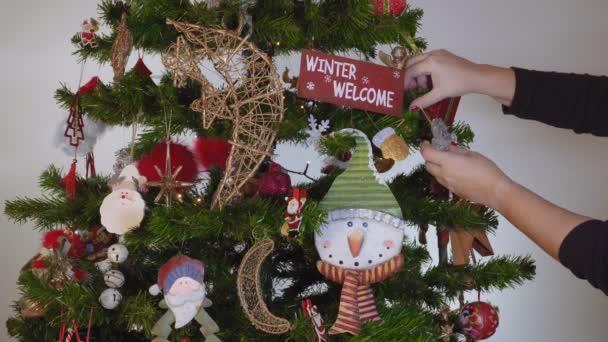 Ženská ruka visí sezónní ozdoby na vánoční stromeček s osvětlením. Slavnostní barevné dekorace před osvětleným umělý vánoční stromek s zimní zdravice visící z brunch