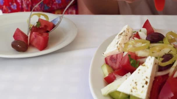 Řecký salát, který se podává na bílém nádobí. Servírují se lžičkou xoriatiki v řeckém salátu se sýrem feta, rajčatovou okurkou a petržel na řecké taverně s bílým plátěnou ubrus.