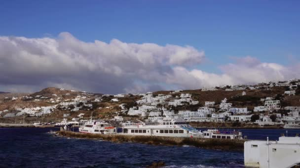 Mykonos, Greece moored ships against Greek island landscape background. Delos Island tourist ships with background of whitewashed low rise traditional Mykonean houses at Mykonos Town (Chora).