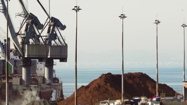 Nagy motorizált daruk a tengeri kikötők kirakodására rakomány hajók. Emelt kilátás a hajó parti daru s rakomány kereskedelmi horgonyzási kikötő mólón Thessaloniki port, Görögország.