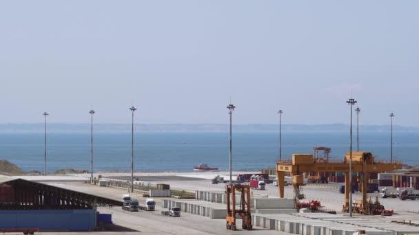 Tengeri kikötői terminál konténeres rakományterüll fuvarozókkal. Halmozott konténerek, nagy kikötői daru t mozgó egymásra rakható konténer jármű kereskedelmi veszteglő Dock mólón Thessaloniki kikötő, Görögország.