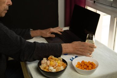 Older man's hands teleworking from home at the window