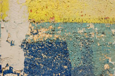 Blue and yellow paint strokes on grunge concrete wall.