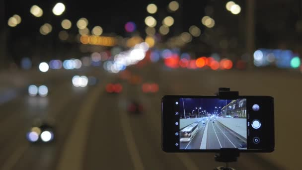 The smartphone is installed over the road. On it the movement of cars is removed, against a background of beautiful lights.
