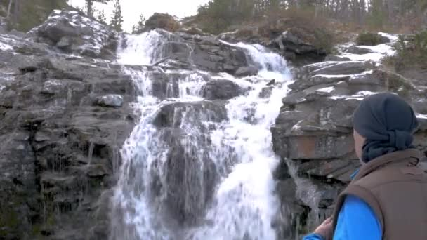 Male traveler is resting by the beautiful mountain waterfall. Close-up. He is talking on the radio with his friends.