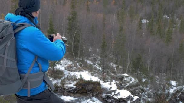Fotograf cestuje v horách. To se nachází na vyvýšeném místě a obdivuje nádherný výhled. se dívá na hory a les. Fotí krajiny na kameru.