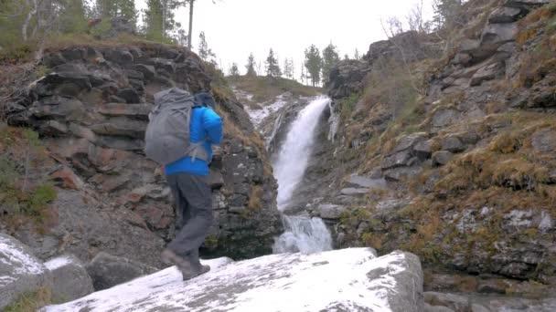 Turistický batoh vyleze na skále na horský vodopád. Došel konec trasy. Aktivní dobrodružství a cestování.