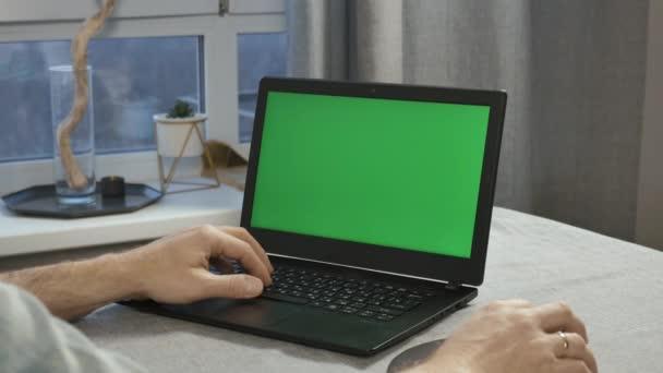 Detail z mužských rukou, které pracují na notebooku s zeleným plátnem.