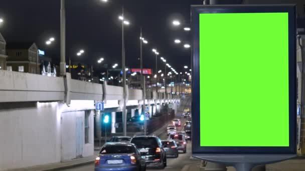 Billboard se zelenou obrazovkou, umístěný na rušné ulici. Auta se pohybují večer.