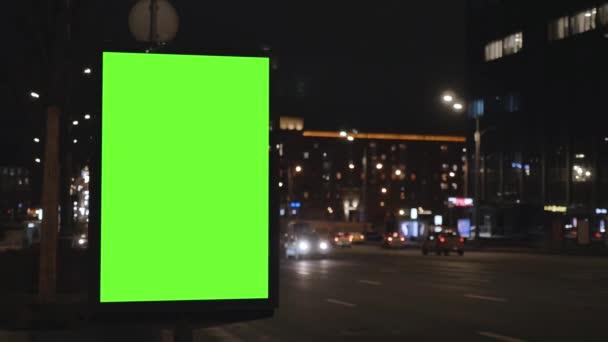 Plakatwand mit grünem Bildschirm an einer belebten Straße. Autos fahren am Abend.