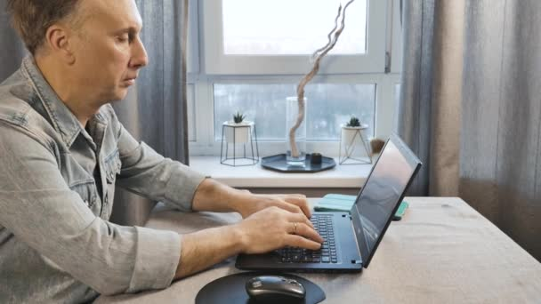 A middle aged man working on a laptop. Freelancer works at home. Side view.