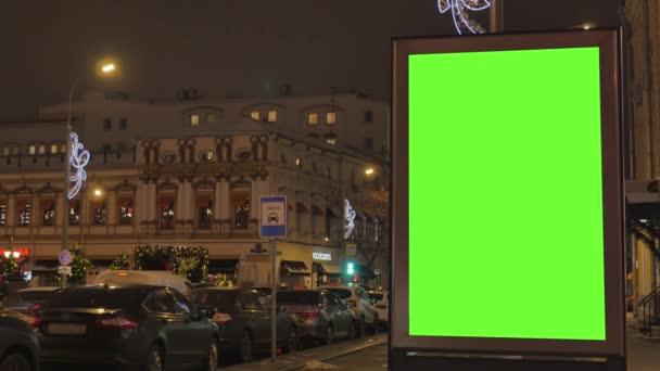 Egy nagy hirdetőtáblán az utcán egy zöld képernyő díszített, az ünnep.