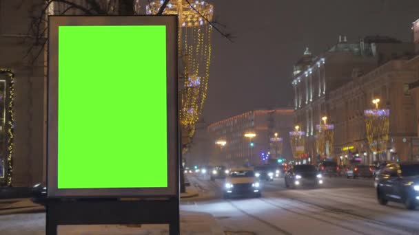 Egy óriásplakát, egy zöld képernyő egy mozgalmas ünnepi utcában.