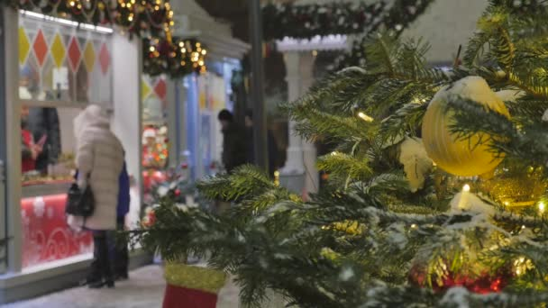 Christmas fir tree decorated with toys. Out of focus people go shopping.