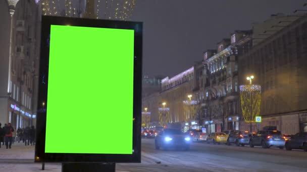 Velký billboard s zeleným plátnem na ulici zdobené pro dovolenou.
