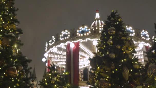 Vánoční strom jedle s detail hračky. Dekorace z města na dovolenou. V pozadí rozostřené otočí kolotoč, na které děti jezdit. Slavnostní atmosféru.